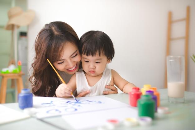 幸せな家族の母と娘が一緒にペイントします。アジアの女性は彼女の子供の女の子を助けます。
