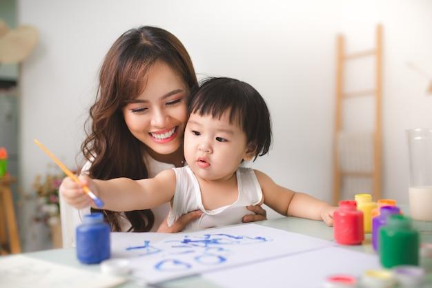 행복한 가족 엄마와 딸이 함께 페인트합니다. 아시아 여자는 그녀의 어린 소녀를 돕습니다.