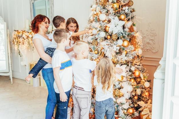 Счастливая семья, мать и пятеро детей, украшающие елку в канун рождества у себя дома. мама дочерей и сыновей в светлой комнате с зимним декором. рождество новый год время для празднования.