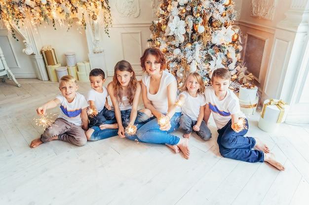 幸せな家族の母親と自宅でクリスマスイブにクリスマスツリーの近くで線香花火をしている5人の子供