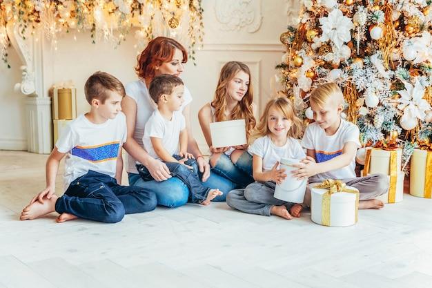 Счастливая семья, мать и пятеро детей отдыхают, играя у елки в канун рождества дома. мама, дочери, сыновья в светлой комнате с зимним декором. рождество новый год время для празднования