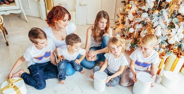 Счастливая семья, мать и пятеро детей отдыхают, играя у елки в канун рождества дома. мама, дочери, сыновья в светлой комнате с зимним декором. новогоднее время для празднования. баннер