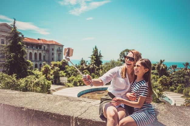 Счастливая семья, мать и ее очаровательная маленькая дочь на летних каникулах, делающих селфи со смартфоном
