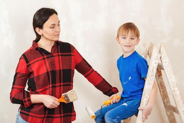 Счастливая семья, мать и сын красит стену.