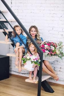 幸せな家族の母と2人の美しい女の子の娘が家で一緒に花で休日に