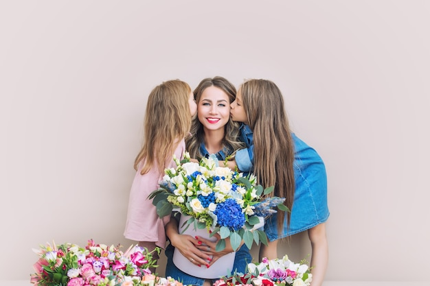 幸せな家族の母と2人の美しい女の子の娘が一緒に花で休日に
