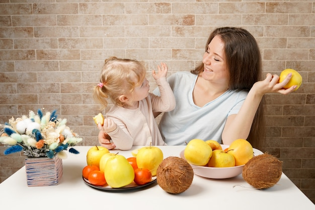 Happy family mother and child baby daughter with healthy food fruits on the kitchen indoor
