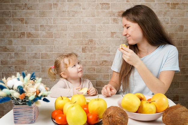 Happy family mother and child baby daughter with healthy food fruits on the kitchen