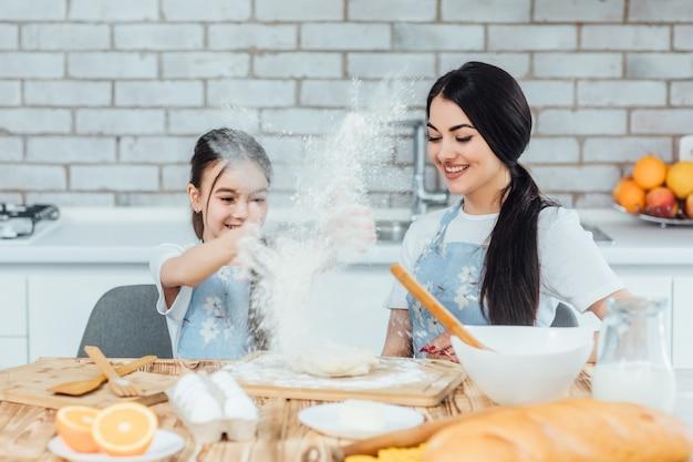 La madre di famiglia felice e la figlia del bambino cuociono impastare la pasta in cucina
