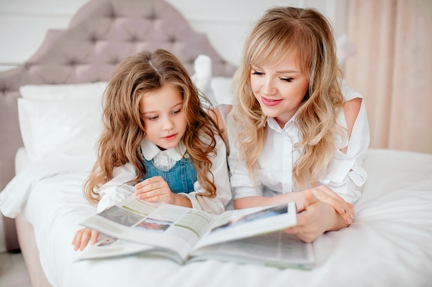 Happy family mother and child daughter reading holding book lying in bed, smiling mom baby sitter telling funny fairy tale to cute preschool kid girl