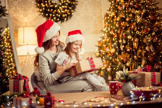 A happy family mother and child pack christmas gifts