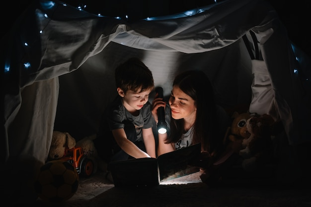 Happy family mother and child son reading a book with a flashlight in a tent at home. family concept