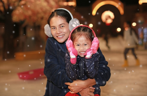 Happy family of mother and cute little child girl has a fun in snow, winter time.