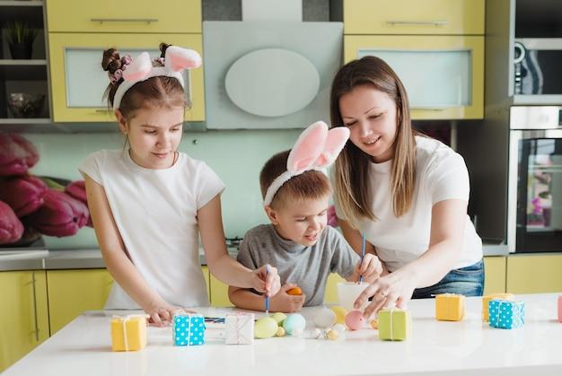 幸せな家族:母娘とウサギの耳を持つ息子が休日の準備をしていて、家の居心地の良いキッチンで卵を着色しています。イースター休暇の準備