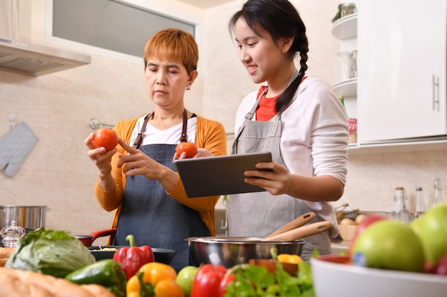 Happy family of mother and daughter using digital tablet and cooking in kitchen making healthy food together feeling fun