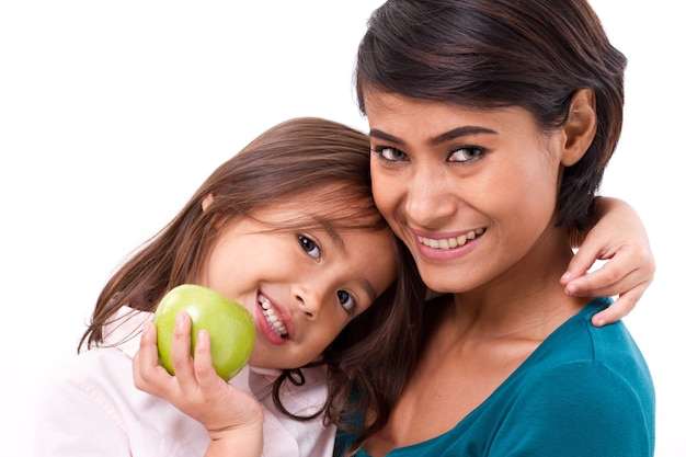 Happy family, mother and daughter with raw organic green apple, concept of healthy food
