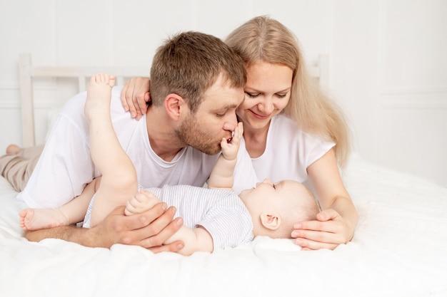 幸せな家族の母親の父と赤ちゃんが楽しんで、赤ちゃんが前景を這う
