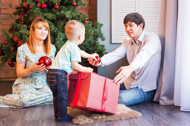 Счастливая семья, мать, отец и ребенок маленький ребенок, играя зимой на рождественские праздники.