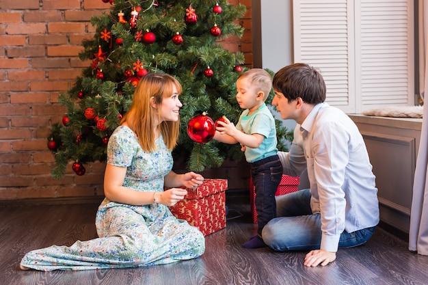 クリスマス休暇のために冬に遊ぶ幸せな家族の母、父と赤ちゃんの小さな子供