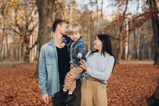 Счастливая семья, мать, отец и ребенок на осенней прогулке в парке