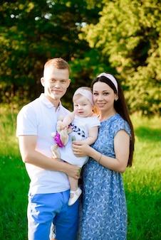 幸せな家族:日没の自然の母父と子娘