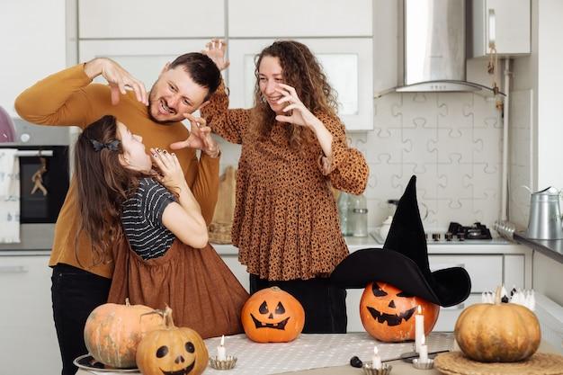 Счастливая семья, мать, отец и дочь, празднование хэллоуина дома