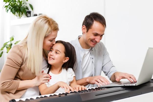 幸せな家族、母、父と娘が家でピアノを弾く、家族関係の概念。音楽学校と音楽家族。