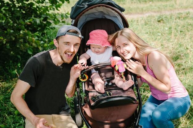 행복한 가족 : 어머니, 아버지와 여자가 그녀의 아기와 함께 산책 및 운반.