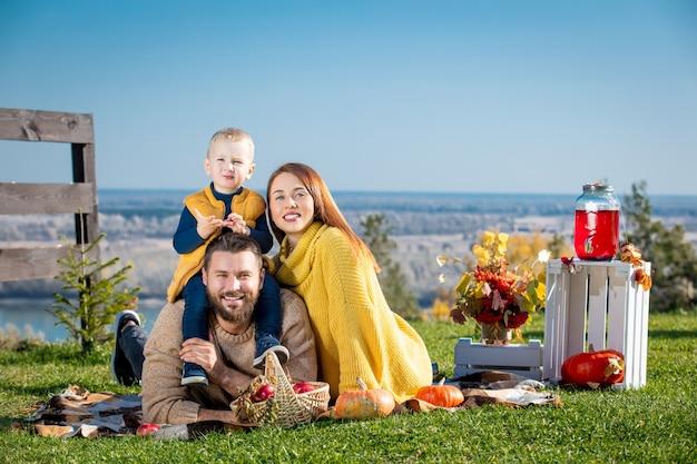 행복한 가족 어머니 아버지와 작은 아기 아들이 함께 자연에서 격자 무늬 호박과 함께 피크닉
