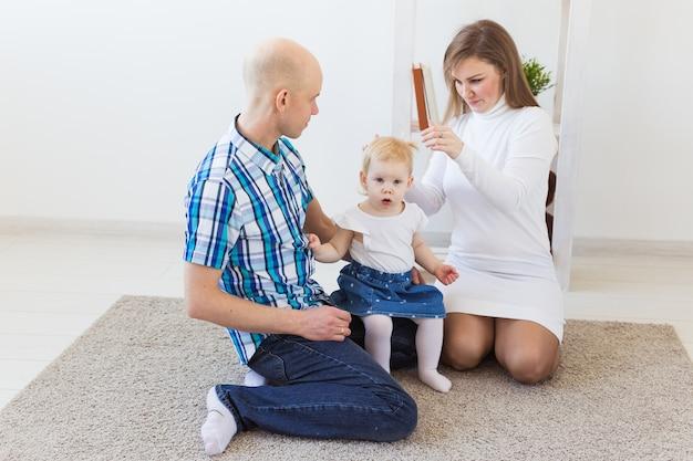 Счастливая семья, мать, отец и их ребенок вместе в гостиной дома.