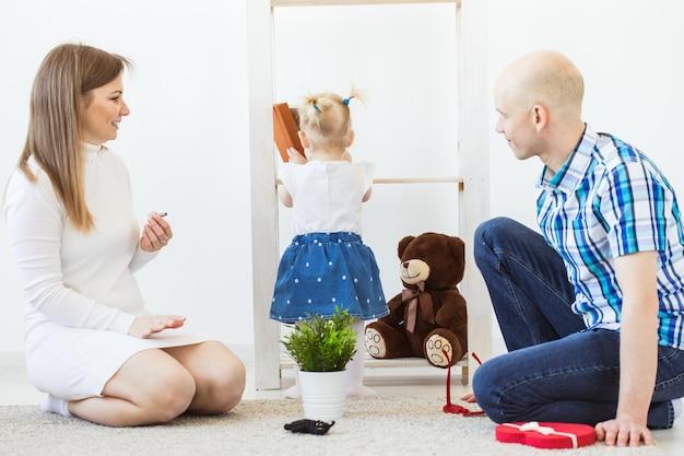 Счастливая семья, мать, отец и их ребенок вместе играют в гостиной дома.