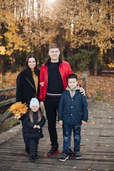 幸せな家族の母、父と2人の子供が秋の公園のフルショットで屋外で一緒にポーズをとる。笑顔の子供と前向きな感情を持つ黄色の葉を持って一緒に歩いている両親