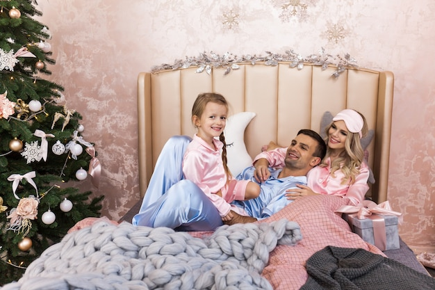 Happy family mother father and child on christmas morning in bed in pajamas