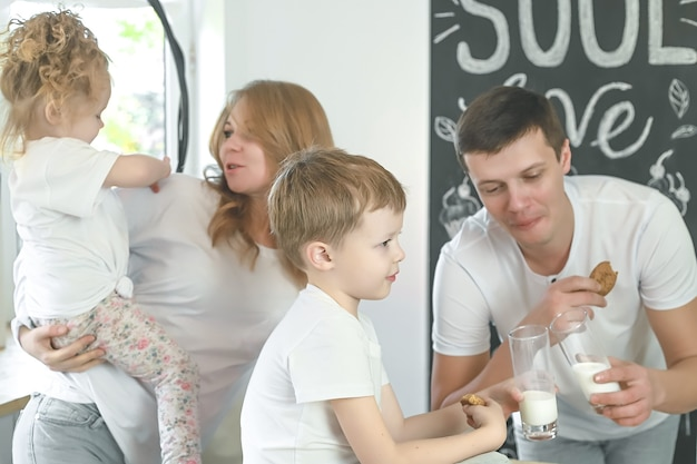 Happy family mother father child daughter and son having breakfast at home