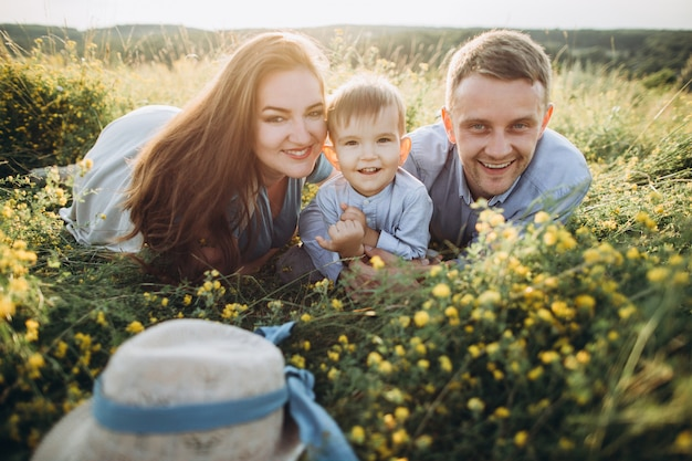 Happy family: mother, father, children son on nature at sunset