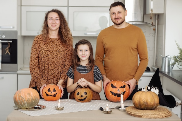 Happy family mother father and daughter celebration of halloween at home