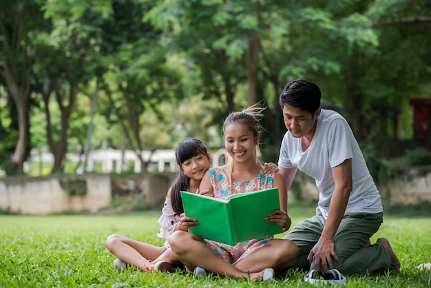 Happy family mother, father and daughter read a book in the park
