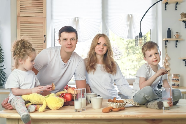 Happy family mother father daughter an son having breakfast at home vitamine breakfast in kitchen