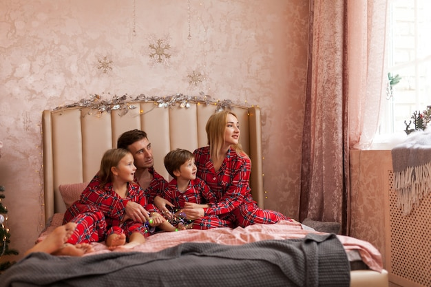 Happy family mother father and kids on christmas morning in bed in pajamas