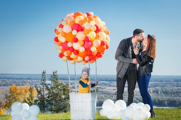 Happy family mother father and son together in nature with balloon for air travel