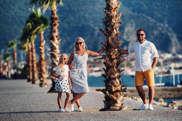 Happy family of mother father and young daughter stands under palm tree with rised hands.