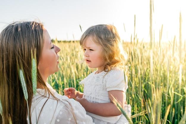 幸せな家族、日没時に黄金の麦畑でかわいい赤ちゃんとドレスを着た母親。夏の日。