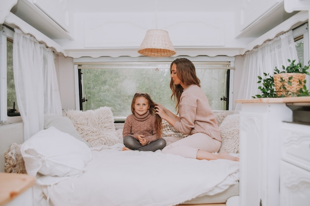 Happy family - mother and little daughter relaxing in countryside inside white scandinavian rustic camper van interior.