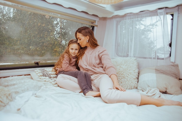 Happy family - mother and little daughter relaxing hugging and having fun in countryside