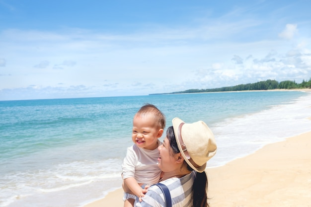 Happy family. mother playing with cute smiling little asian 18 months old baby boy child on sunny day against white sand beach & blue sky
