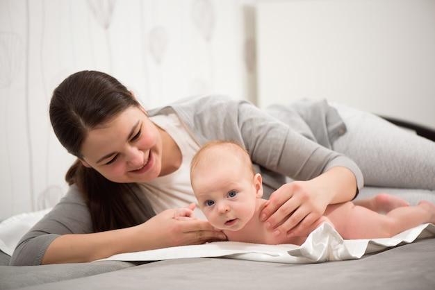 행복한 가족. 침실에서 그녀의 아기와 함께 재생하는 어머니.