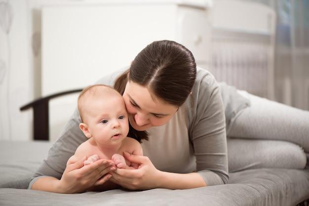 Счастливая семья. мать играет со своим младенцем в спальне.