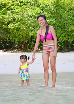 Happy family - mother and small baby daughter on sea beach.