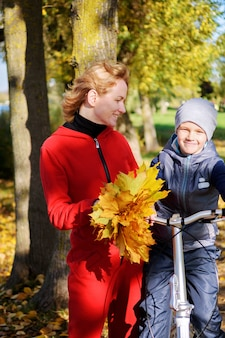 Happy family mother and son communicate on an autumn walk. mother teaches her son to ride a bicycle.