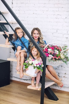 Happy family mother and two beautiful girls daughters on holiday in flowers together in the home